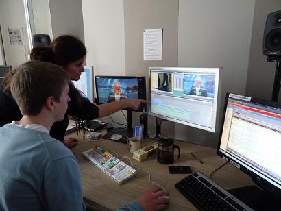 Un élève essaye le montage video accompagnée par une professionnelle de l'équipe